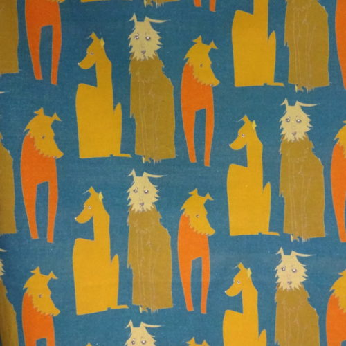 "wicked imp studio limited edition cotton fabric ""hanging around hounds"" 3 drawn sitting dogs done in yellows and orange with a blue background. Close up detail"